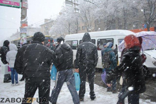 Снег и люди на остановке траспорта в Запорожье
